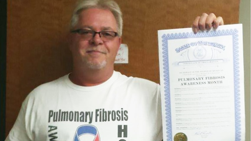 Larry holding proclamation for pulmonary fibrosis awareness month