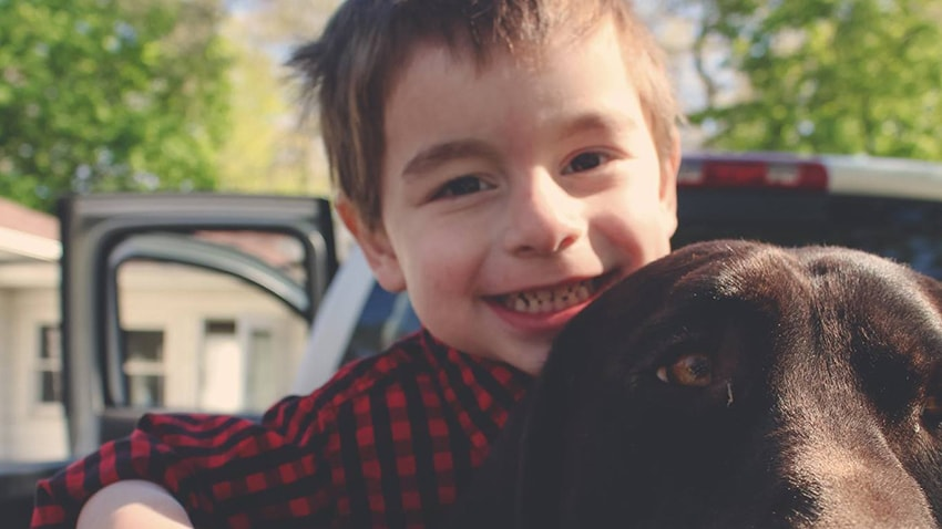 Owen, a pediatric heart transplant survivor, and his dog in the back of a truck
