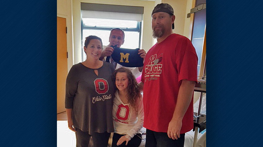 Olivia and her family of Ohio State fans with their U-M doctor