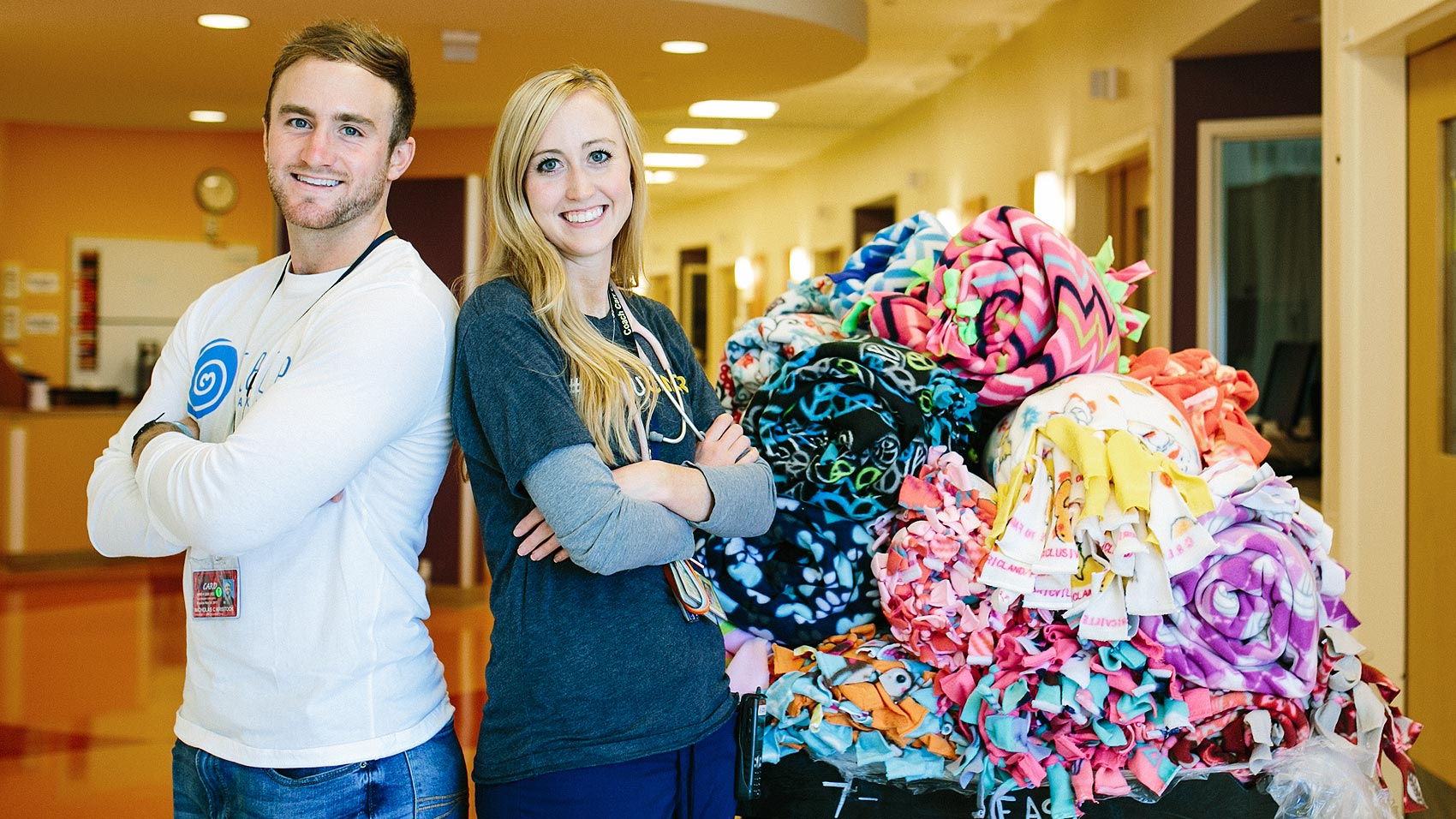 Tara and Nicholas Kristock and a pile of donated fleece blankets