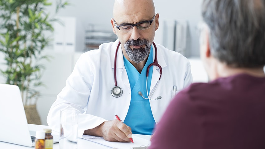 doctor with white coat sitting with stethoscope around his neck and blue shirt talking with patient with short grey hair and maroon shirt