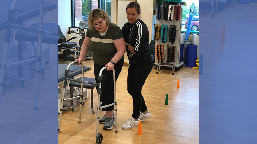 Patient using walker with therapist