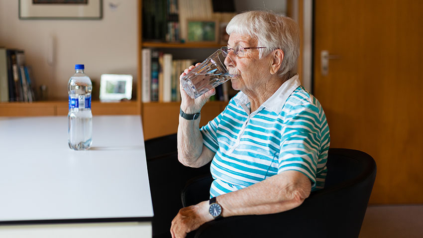 Patient at desk drinking a fluid