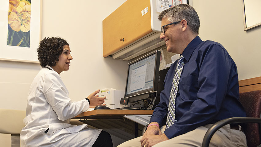 Kevin Bergquist in a clinic exam room with Dr. Sara Saberi