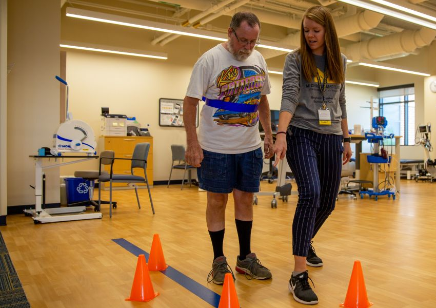 Marty Marchack walks between orange cones with a physical therapist Cassie Van Dyke.