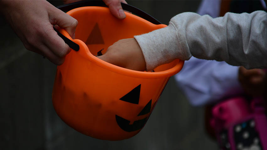 Orange pumpkin bag of candy with kids reaching inside