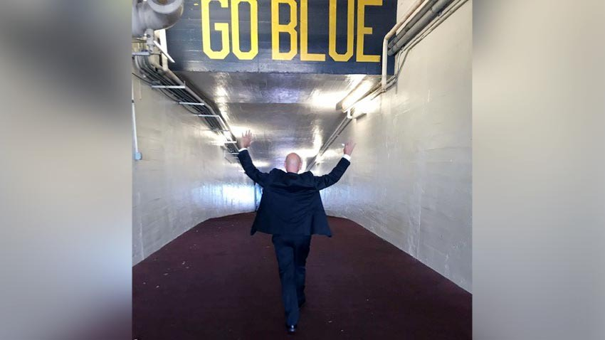 Patient walking down Go Blue tunnel with hands up in the air