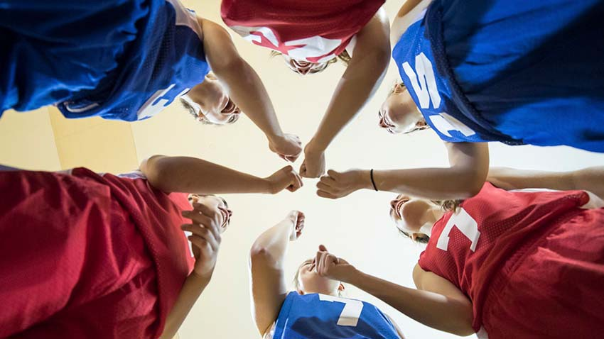 Girls in red and blue jerseys standing in a circle with fist together in the center