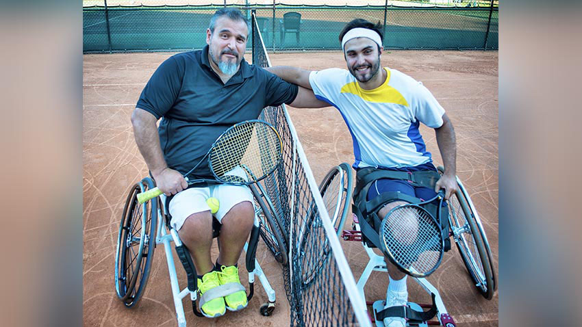 Men in wheel chairs on tennis court