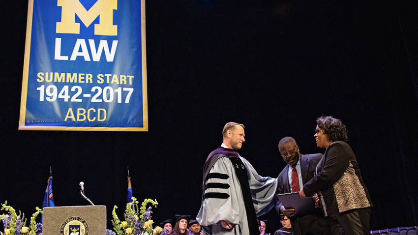 Parents being handed law degree at U-M law school ceremony