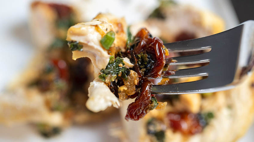 Cherry, kale and feta stuffed chicken on a fork