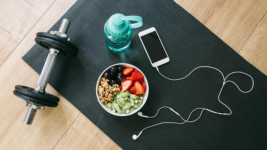 image of weight phone headphones bowl of fruit and water bottle.