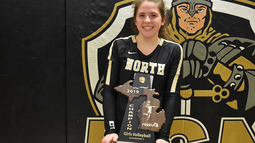 Emily posing with volleyball trophy