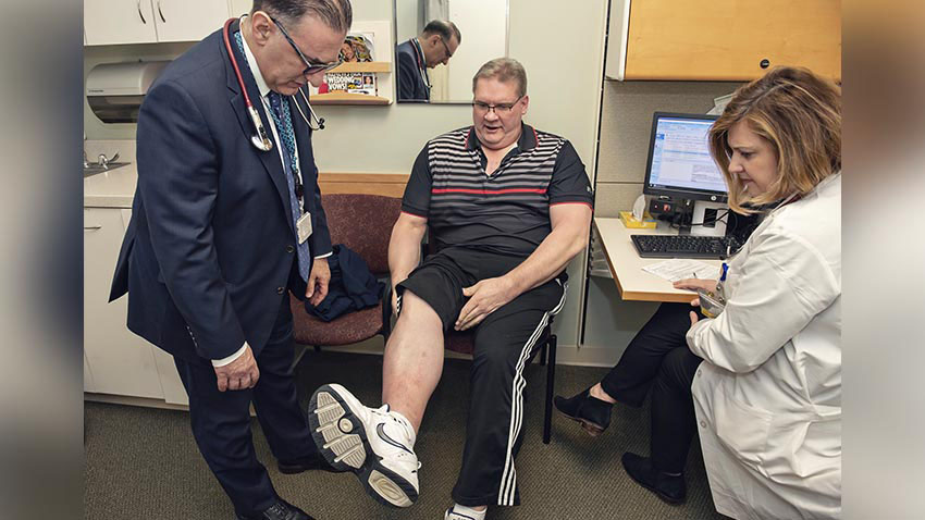 Doctor and nurse looking at patient leg