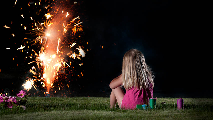 little girl sitting on grass watching fireworks