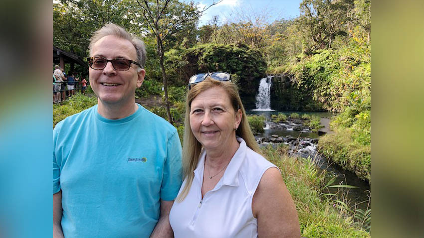 husband and wife near a waterfall
