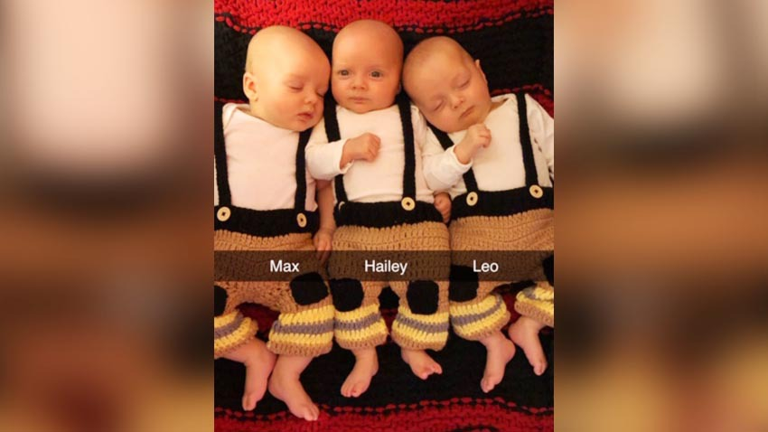 newborn triplets dressed in firefighter outfits