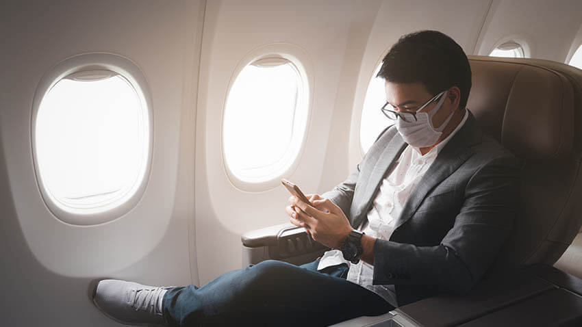 Male on airplane with mask using phone