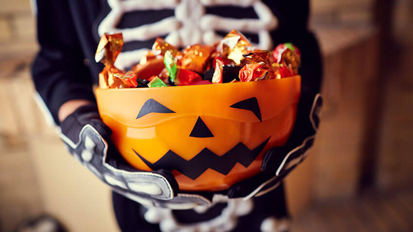 Kid holding pumpkin bowl of candy in skeleton costume