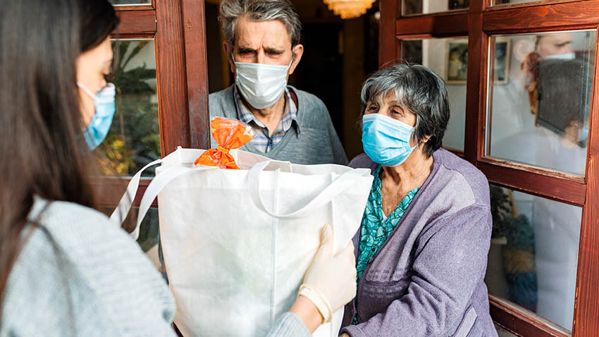 person delivering forceries to elderly couple