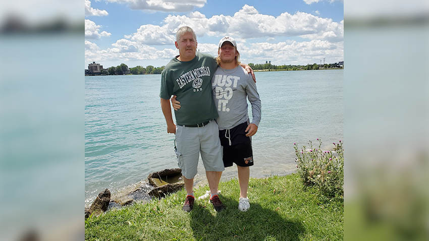 two males in front of a lake