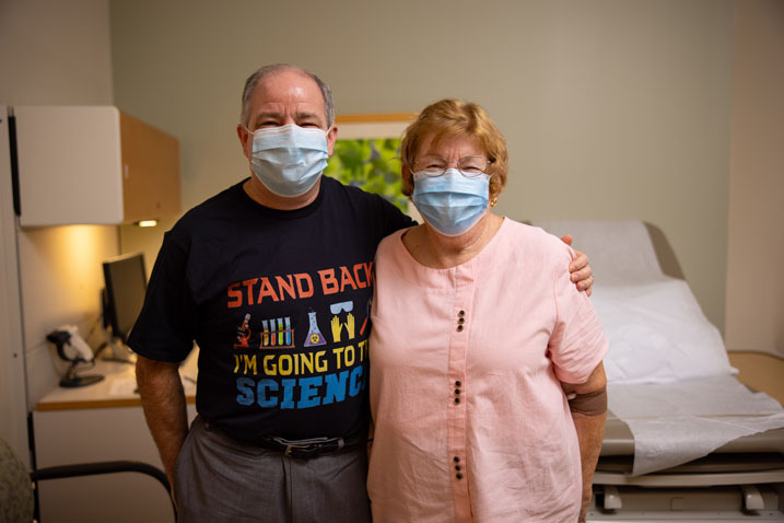 son wearing a black shirt and a blue mask posing with his mother who is wearing a blue mask and pink shirt