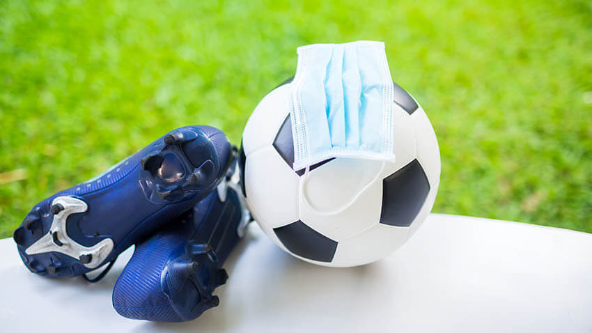 Soccer ball with cleats and mask near green field
