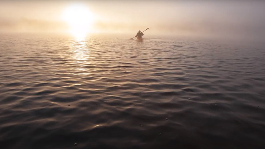man paddling in boat on open water with sun