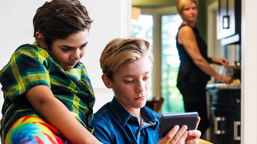 Parent looking concerned at children watching phone screen a lot