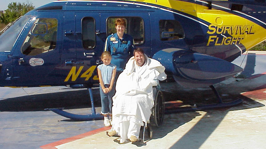 survival flight patient and daughter with employee in front of yellow and blue Michigan helicopter