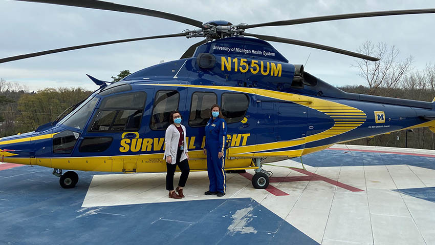 two omen in front of helicopter that's blue and yellow with masks on