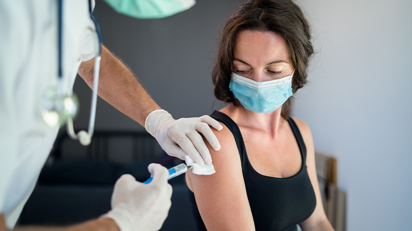 white woman getting vavvine in arm with mask on from practitioner with white gloves and stethoscope