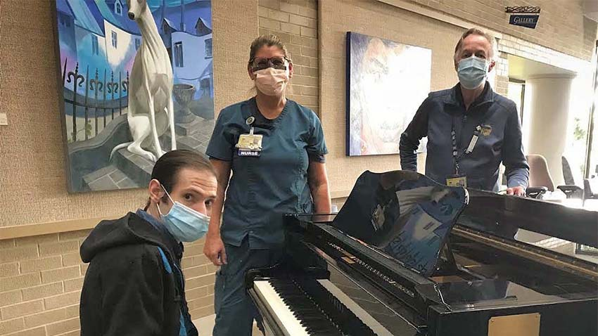 man sitting at piano with mask on and nurse with mask on standing near him and man with mask on standing across piano