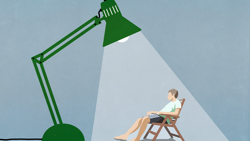 cartoon man under spotlight of green lamp sitting in chair
