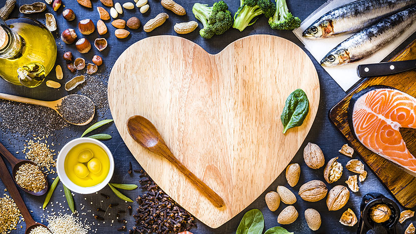 Heart shaped cutting board with wooden spoon and food around