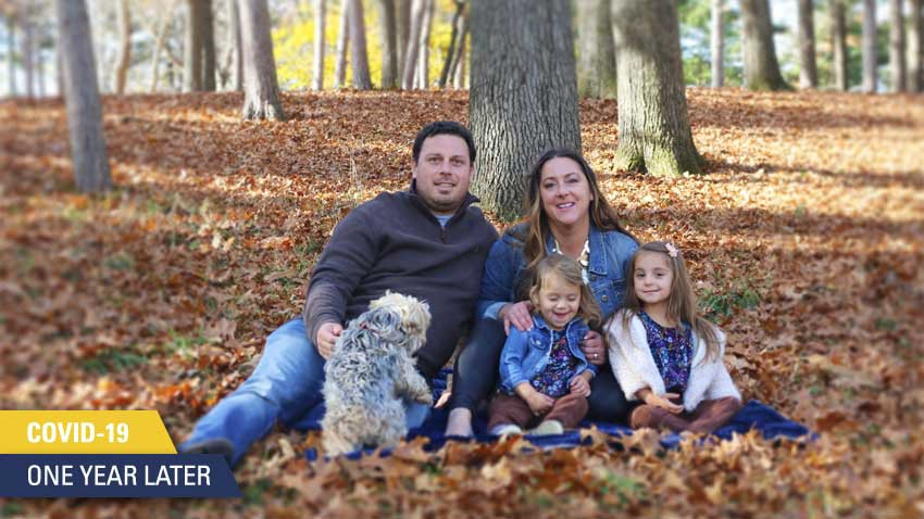 family of 4 with dog sitting against tree on fall leaves