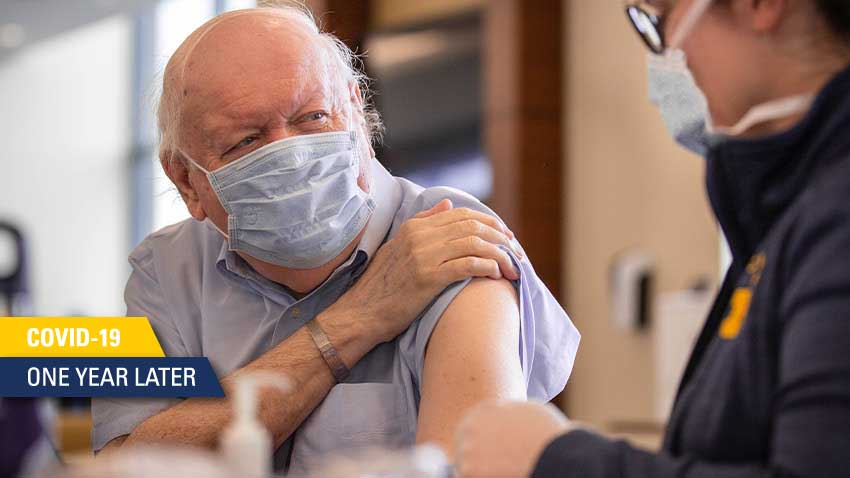 older man with white hair and blue face mask on lifting sleeve on blue shirt to get vaccine from worker