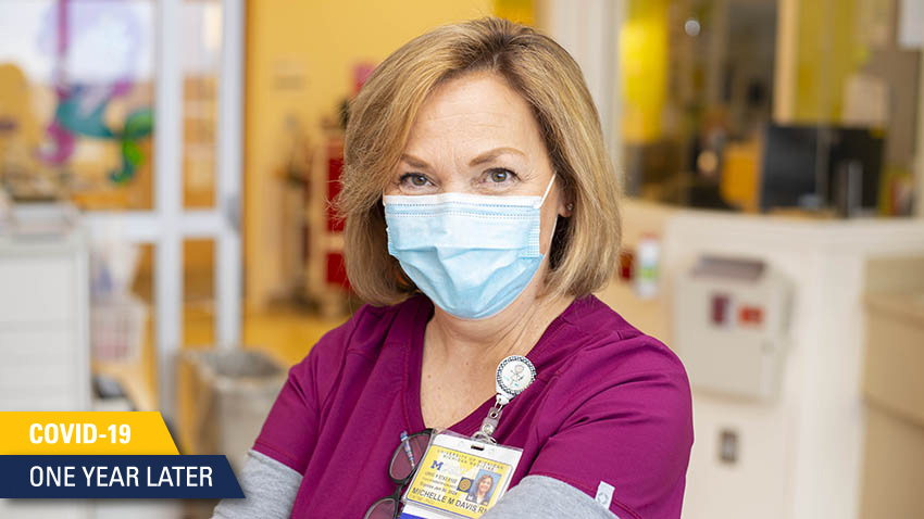 nurse in maroon scrubs and light blue mask smiling at camera