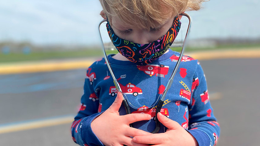 child looking down at stethoscope on his chest while wearing mask outside and wearing blue shirt with firetrucks on it