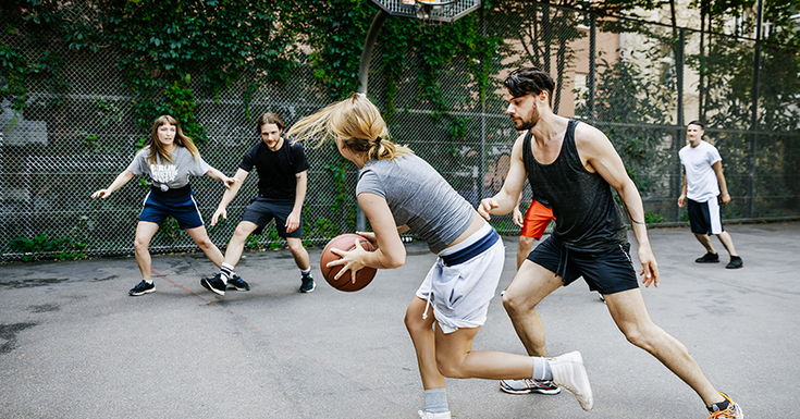 Men and women playing basketball