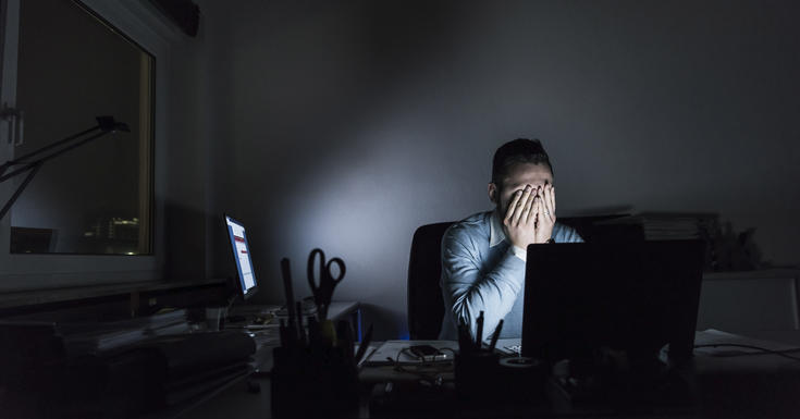 Employee sitting alone in dark room with hands over face