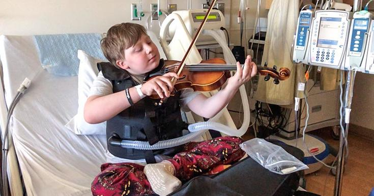 Boy with cystic fibrosis playing violin