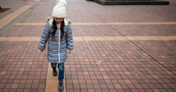 Little girl walking on brick path