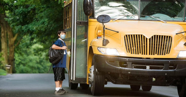 Child with brown hair and mask on in front of open doors of school bus wearing backpack