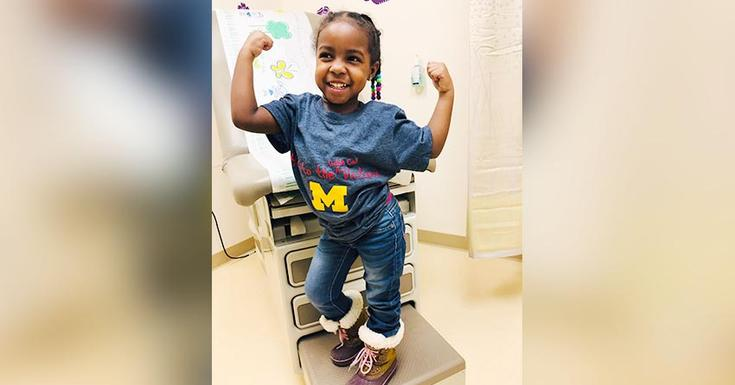 little girl doing muscle pose in doctor's office wearing a blue Michigan shirt