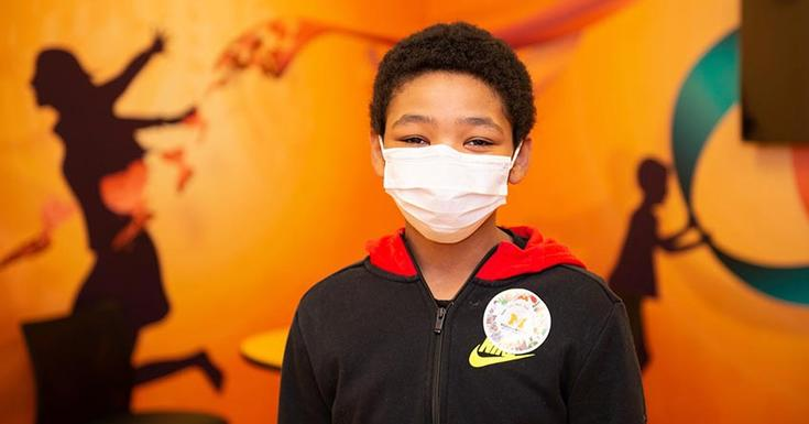 child in hospital with mask on and orange background
