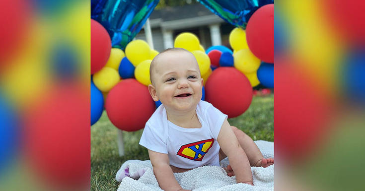 baby on law with red yellow and blue balloons in background