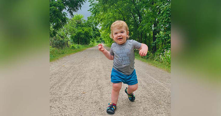 Toddler walking on dirt path surrounded by trees