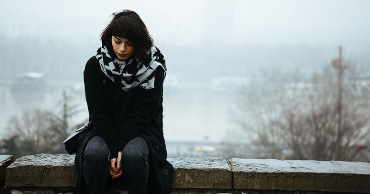 young woman lookin down at the ground wearing black on a foggy day