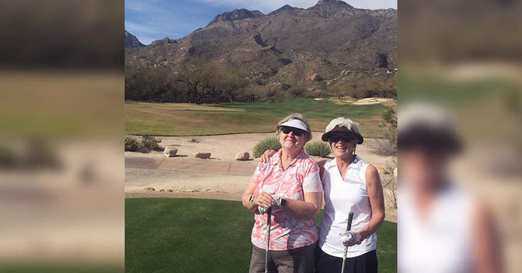 two ladies golfing in front of a mountain wearing hats